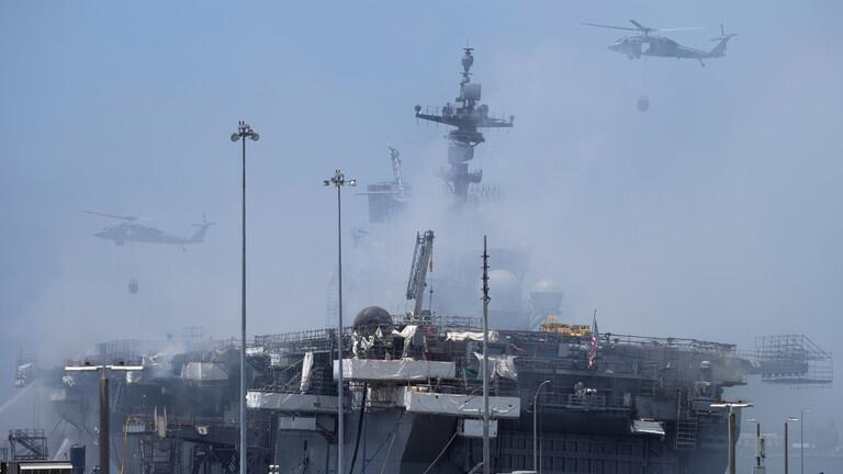 直升机在往冒烟的船体上洒水