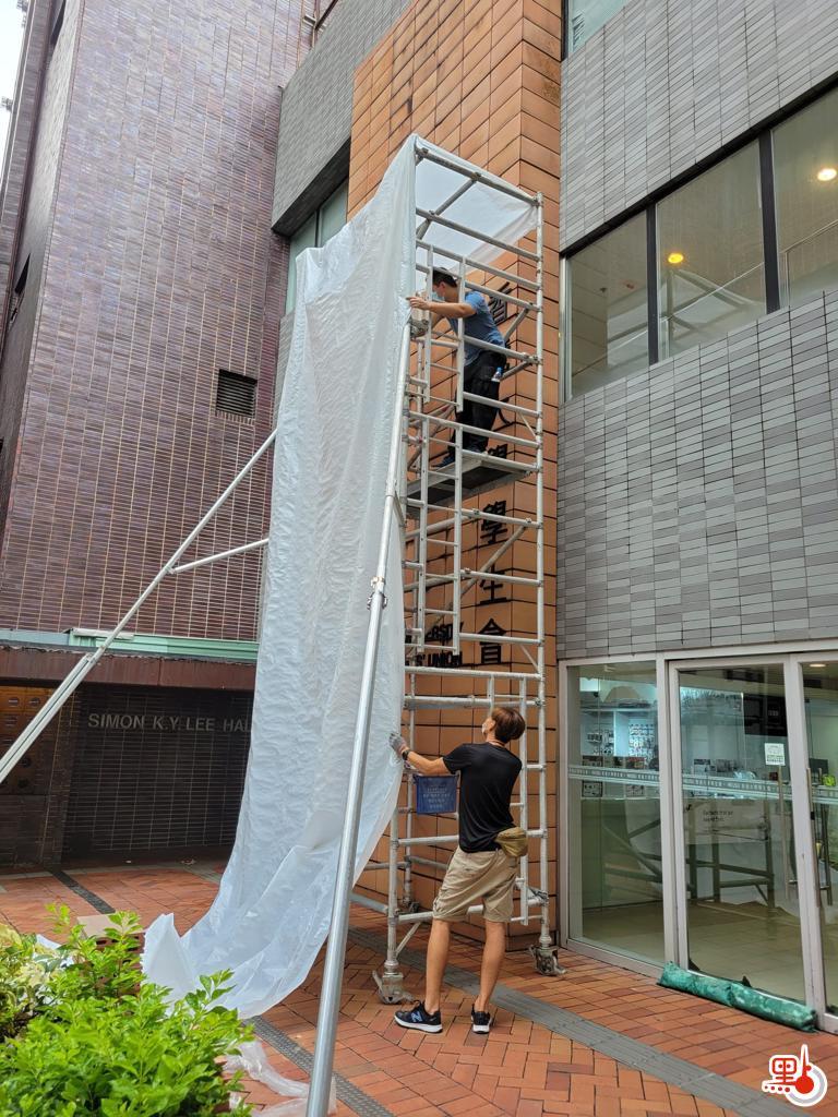 """工作人员将大楼外墙的""""港大学生会""""暂时遮盖"""
