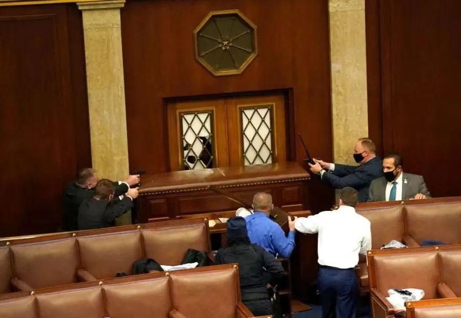国会安保人员拔枪与特朗普支持者隔着门对峙。