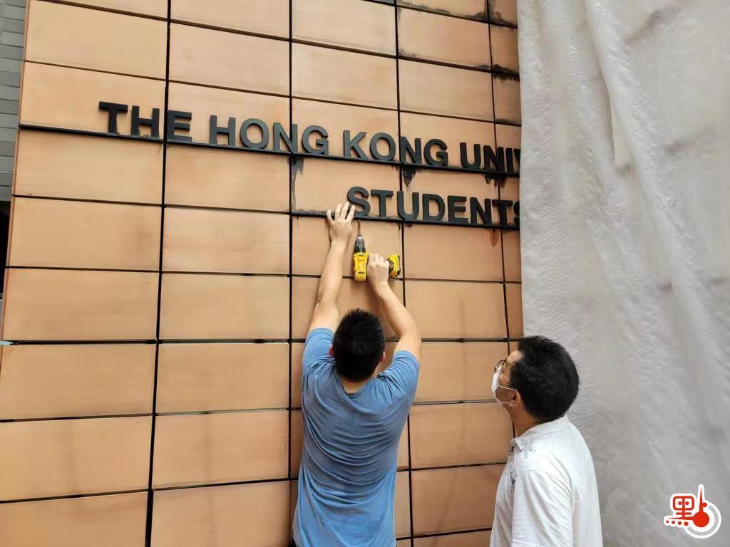 """港大派出工作人员清除办事处门口的中英文字样""""学生会""""。"""
